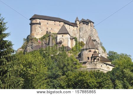 Orava Castle on a background of green trees and blue sky