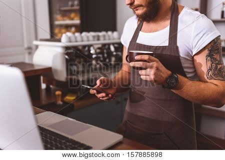 Confident arista resting in coffeehouse. He is using mobile phone and holding cup of coffee. Man is standing near laptop