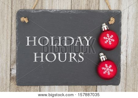 Old fashion Christmas store message A retro chalkboard with Christmas ornaments hanging on weathered wood background with text Holiday Hours