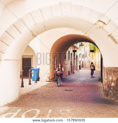 Arco Italy - September 20 2016: Teenage girl riding a bicycle in the streets of Arco Italy. Another female cyclist is going in the opposite direction.