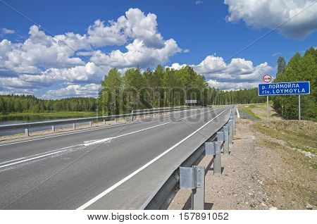 A road sign with the name of the Loymoyla river on a bridge on the federal highway A121. Sunny day in June. South Karelia Russia.