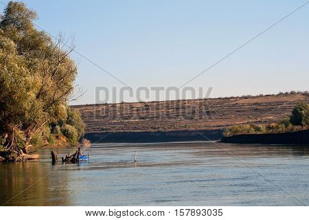 Fall in October on the arms (channels) of the Danube River. Here arm (canalu) Calin Jordan. Specific autumn meadow vegetation, trees, leaves, birds, fishermen
