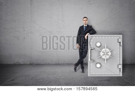 A businessman in a confident pose standing next to the safe on the background of the grey wall. Business and finance. Success and wealth. Protection of funds.