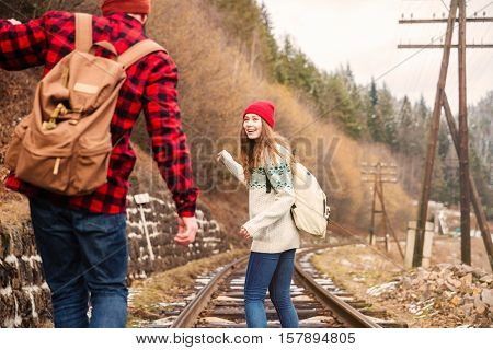 Happy young couple talking and walking on railroad together