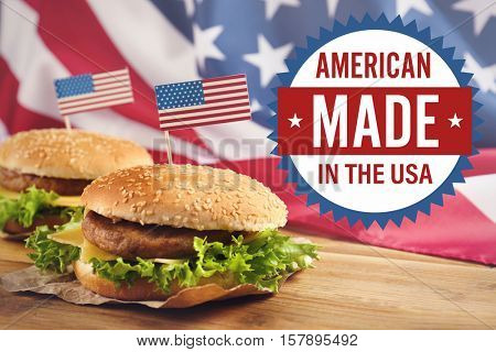 Label with text AMERICAN MADE IN THE USA and tasty burgers on wooden table.