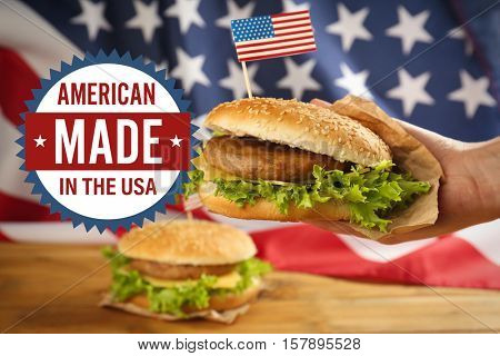 Label with text AMERICAN MADE IN THE USA and male hand holding tasty burger on flag background