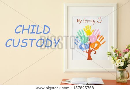 Painting with family palms prints on wall. Text CHILD CUSTODY on wall background