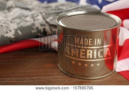 Tin of combat ration with text MADE IN AMERICA on wooden background, closeup. Manufacturing quality concept.