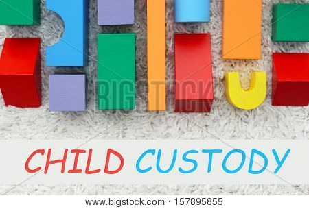 Colorful wooden children building kit with text CHILD CUSTODY on textured background