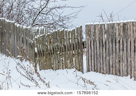 Old wooden fence with snow. Rickety fence after a snowfall.