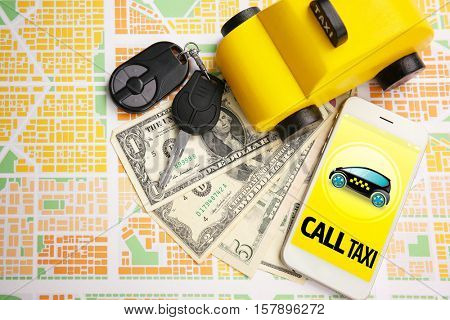 Yellow toy taxi cab, smartphone, money and keys on city map background. Taxi service application on phone screen.