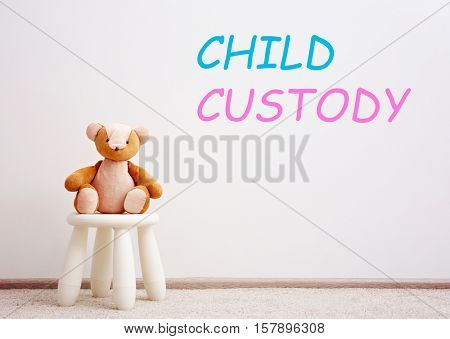 Children stool with toy. Text CHILD CUSTODY on wall background