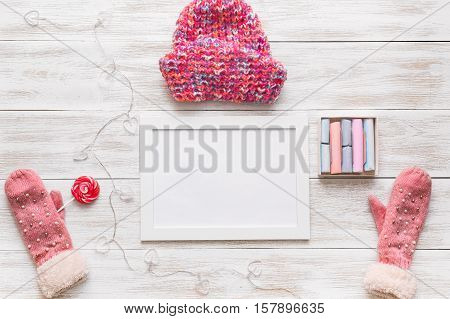 On the white wooden table is perfect set of winter mittens and hat. Bannern space for text. Banner template layout mockup for Christmas Day and New Year Day.