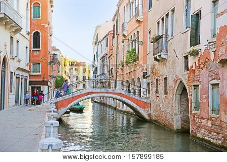 Venice, Italy - October 12, 2016: View of the canal with bridge, boats and colorful houses in Venice