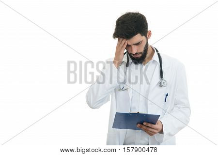Worried young doctor with head in hand on white background.