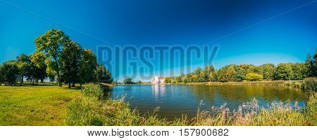 Mir, Belarus. Panoramic View Of Mir Castle Complex From Side Of Lake. Architectural Ensemble Of Feudalism, Ancient Cultural Monument, Famous Landmark In Summer Sunny Day Under Blue Sky, Copyspace.
