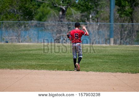 American youth baseball player holding up his hand walking on the field.