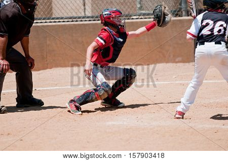 Baseball catcher reaching to catch a wild pitch with umpire behind him.