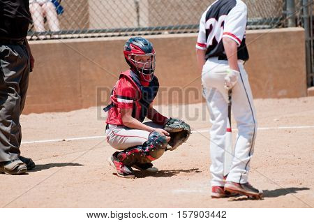 American youth baseball catcher looking at coach for signals with umpire behind him.