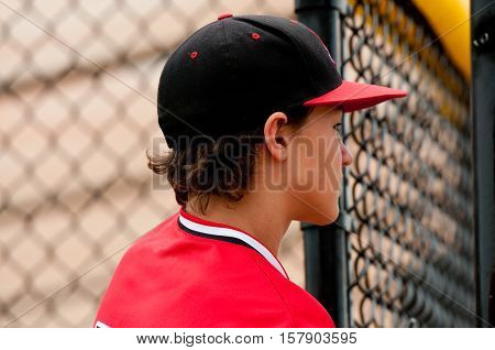 Young American baseball boy inside dugout watching the game.