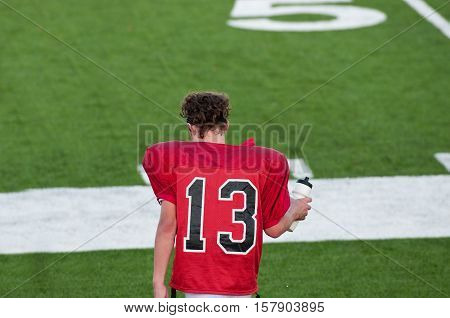 American football boy on sidelines during water during game.