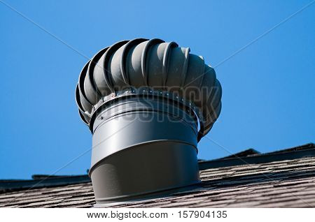 Roof top whirly bird ventilation on top of house with background of blue sky.