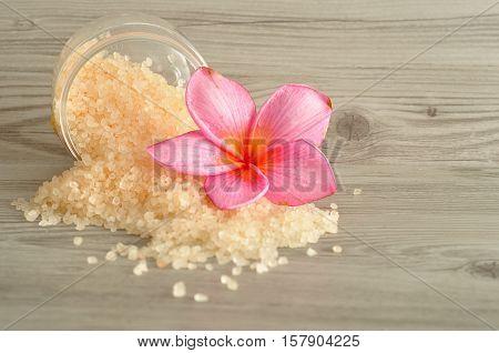 Bath salt with a frangipani flower on a wooden background