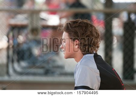 Youth baseball boy sitting in dugout looking sideways.