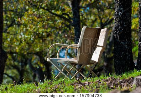 Set of two old yellow metal patio chairs outdoors next to tree at a park.