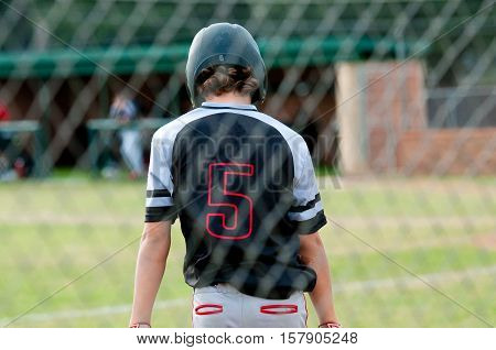 Baseball player in focus behind out of focus baseball cage net.