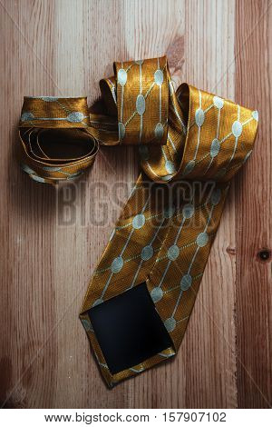 Close up photo of men's tie in wooden background