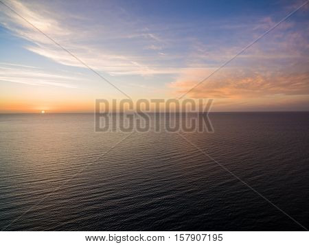 Aerial View Of Sun Setting Over Ocean. Nothing But Skies And Water. Beautifu Scene.