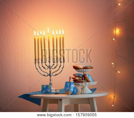 Menorah, dreidels and cookies for Hanukkah on stool in living room