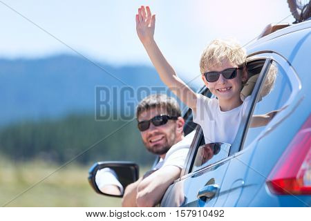 family of two smiling and looking out of the car enjoying road trip in california vacation concept