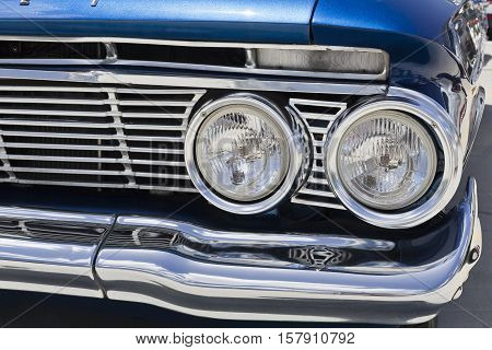 BRISBANE, AUSTRALIA - November 20, 2016: Detail of the front grill of a 1961 Chevy Bel Air car showing the Chevrolet badge and the headlights in Brisbane Australia