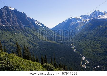 view of valley and rocky mountains range in glacier national park montana usa at going-to-the-sun road poster