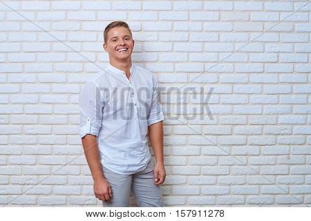 Mid portrait of exhilarated young man against brick wall with fashion look