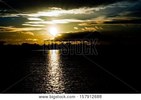 sunset in autumn in November, a bright yellow, brown and black colors, to sit round the sun, clouds heavy different sizes,sun on the horizon,  solar path the pond, very dark background