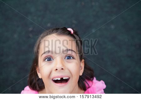 Girl with crazy look and missing tooth looking at camera