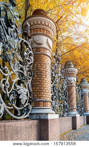 Autumn in St. Petersburg - fence of the Michael Garden in St. Petersburg Russia in autumn day. Autumn architecture view of St. Petersburg landmark framed by autumn yellowed trees