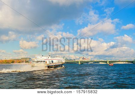 ST PETERSBURG RUSSIA-OCTOBER 3 2016. Trinity Bridge and touristic pleasure boat floating on water area of Neva River in St Petersburg Russia. St Petersburg city landscape in sunny day