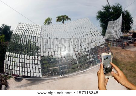 Hand of photographer with smart phone shooting image on blurred Solar cell background.