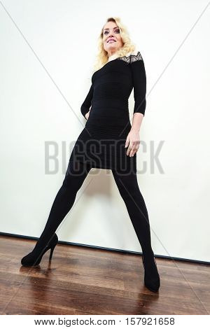 Autumn winter outfit concept. Mid adult blond attractive woman in full length wearing stylish elegant black dress high heels posing studio shot wide angle view