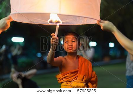 CHIANG MAI, THAILAND, JANUARY 01, 2015 : A young novice Buddhist monk is igniting a floating lantern to celebrate the new year in Chiang Mai, Thailand