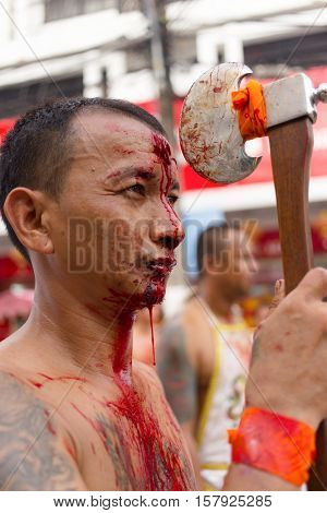 PHUKET TOWN, THAILAND, OCTOBER 09, 2016 : Taoist devotees self harming with an axe for purification during vegetarian festival in Phuket town, Thailand