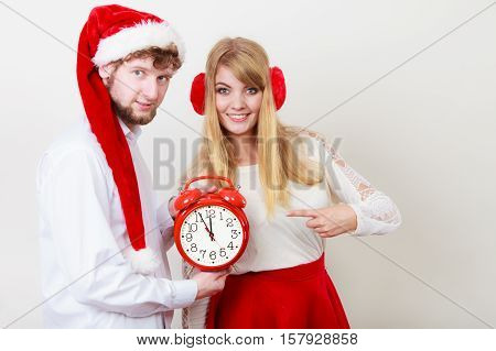Happy cute couple holding alarm clock. Pretty woman in earmuffs and handsome man in santa claus hat on gray. Christmas time season concept.