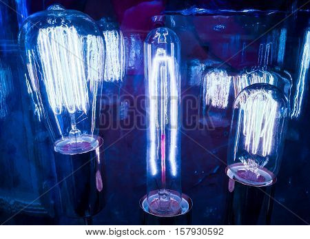 Wide reflections of Blue Light Bulbs Electricity Surging through Filaments of different sizes and shapes showing the evolution of Technology of Lighting