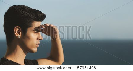 Young handsome brazilian guy with black hair and earring standing in front of ocean and looking into distance shielding his eyes from the bright sun summer day clear sky Rio de Janeiro
