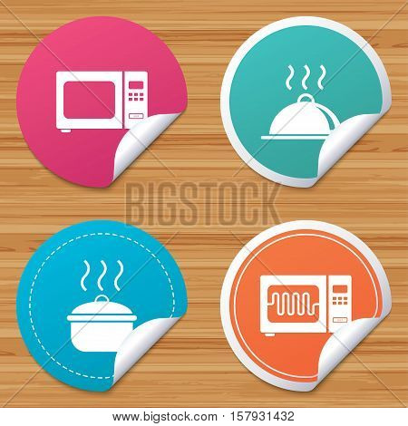 Round stickers or website banners. Microwave grill oven icons. Cooking pan signs. Food platter serving symbol. Circle badges with bended corner. Vector