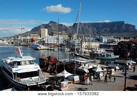CAPE TOWN, SOUTH AFRICA - FEBRUARY 20, 2012: Victoria and Alfred Waterfront, harbor with boats, shops, restaurants and the famous Table Mountain - one of the new seven wonders of nature.